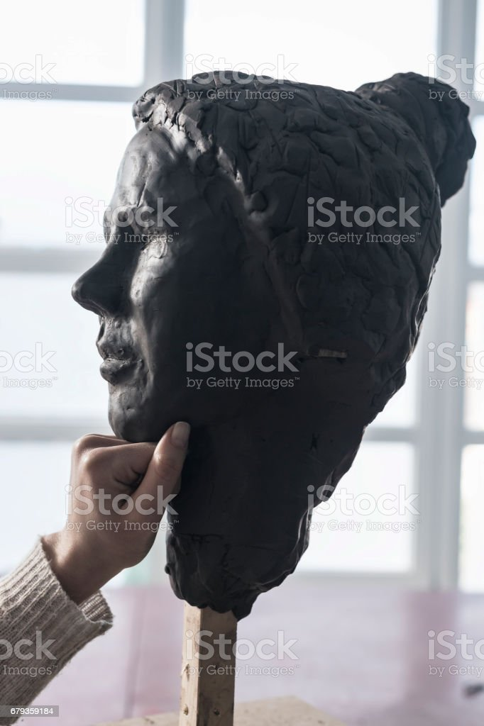 Sculptor holding hand on chin of clay sculpture royalty-free stock photo