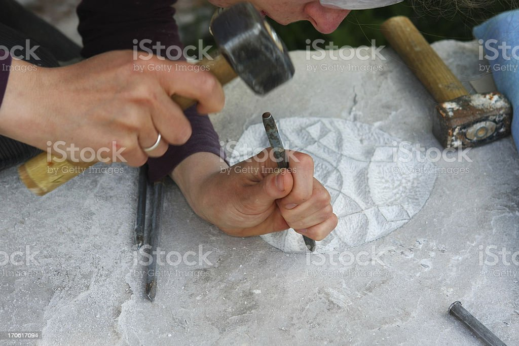 Sculptor making ornament on a stone monolith royalty-free stock photo