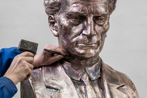 Adding the finishing touches to the bust of a male figure.