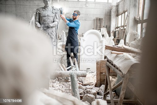 istock Sculptor working with sculpture in the studio 1076794496