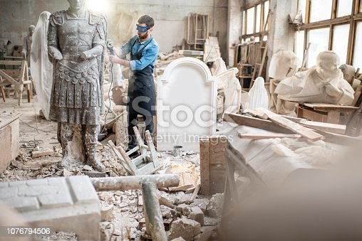 istock Sculptor working with sculpture in the studio 1076794506