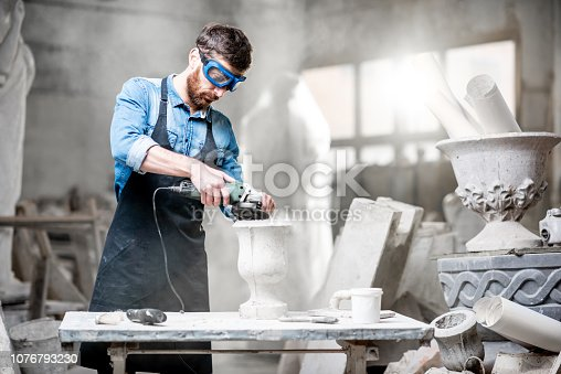 istock Sculptor working with sculptures in the studio 1076793230