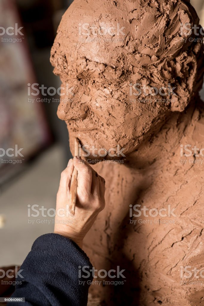 Sculptor's hand working on clay bust detail stock photo