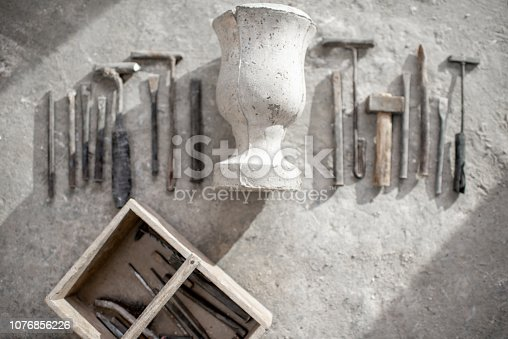Sculptor's working tools with old vase on the floor
