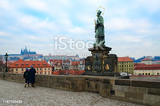 Prague, Czech Republic - January 22, 2019: Sculptural compositions of Charles Bridge. Saint Jan of Nepomuk, heavenly patron of Prague and whole of Czech Republic (1683). Unknown tourists walk along bridge