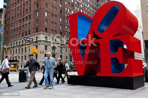 New York City, US - October 9, 2009: People passing the LOVE Sculpture on Sixth Avenue at 55th Street in mid-town Manhattan. The 12-foot New York sculpture was completed in 1970 and installed in 1971.The famous sculpture of Robert Indiana is one of the most photographed icons in the city.