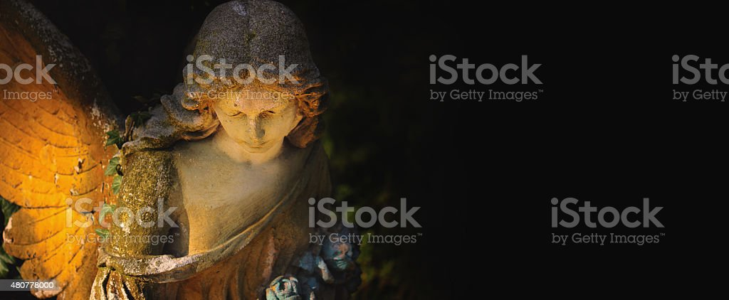 sculpture of an angel with dark background stock photo