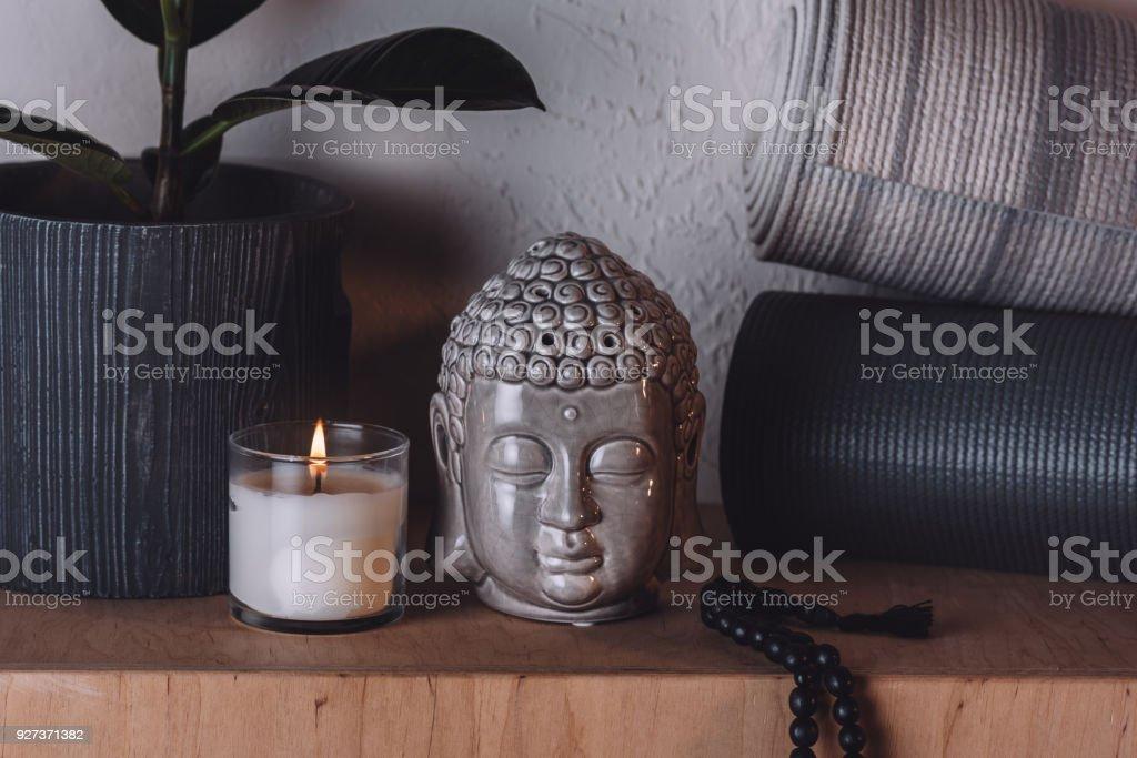 sculpture of buddha head and yoga mats on wooden shelf sculpture of buddha head and yoga mats on wooden shelf Art Stock Photo