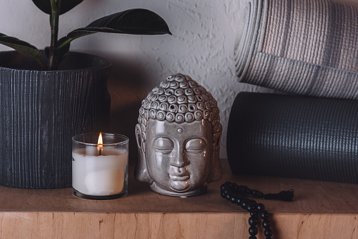 Sculpture Of Buddha Head And Yoga Mats On Wooden Shelf Stock Photo - Download Image Now