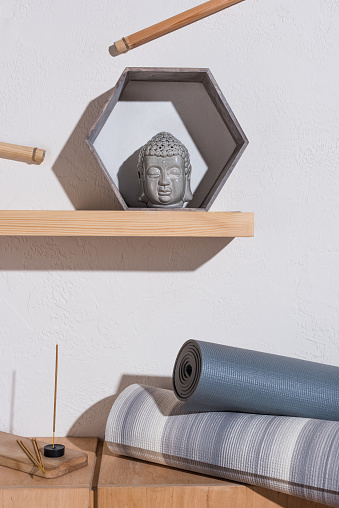 Sculpture Of Buddha Head In Frame And Yoga Mats With Incense Sticks Stock Photo - Download Image Now