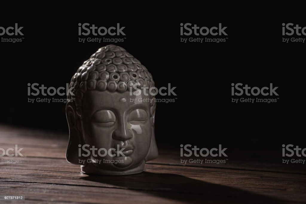 sculpture of buddha head on wooden table - Royalty-free Art Stock Photo