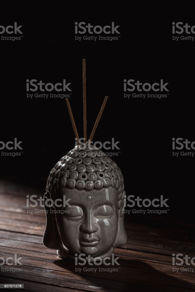 sculpture of buddha head with incense sticks sculpture of buddha head with incense sticks Art Stock Photo