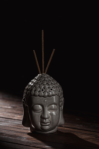 Sculpture Of Buddha Head With Incense Sticks Stock Photo - Download Image Now
