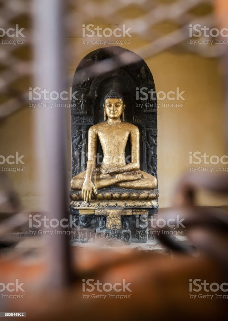 Sculpture of Buddha which is behind bars. stock photo