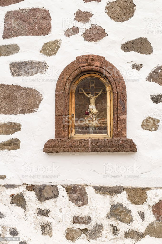 Sculpture of Jesus Christ crucifixion in a niche of wall stock photo