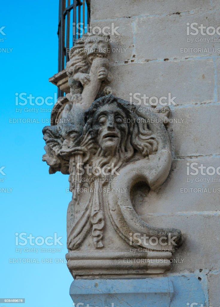 Sculpture over an old building facade stock photo