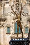 Matera, Italy - September 20, 2019: Matera, European Capital of Culture 2019. Sculpture The surrealist piano by Salvador Dali on Piazza San Francesco and Baroque facade of the Church of St. Francis of Assisi (San Francesco d'Assisi) n the background, Basilicata, Italy,