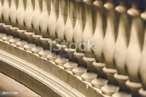 A sculptured bannister railing of small pillars closeup and in selective focus. Aged and vintage look and feel. No people in this high resolution color photograph.