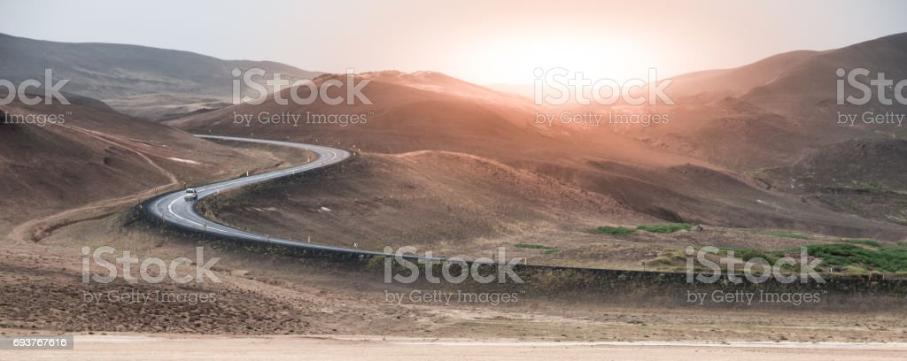 S-curved asphalt road leads to the mountains in volcanic area at sunset time, Iceland. Icelandic road trip theme stock photo