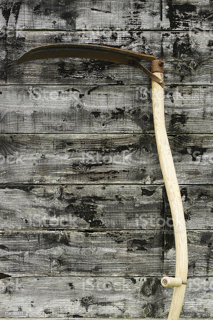 Scythe Against Wooden Boards royalty-free stock photo