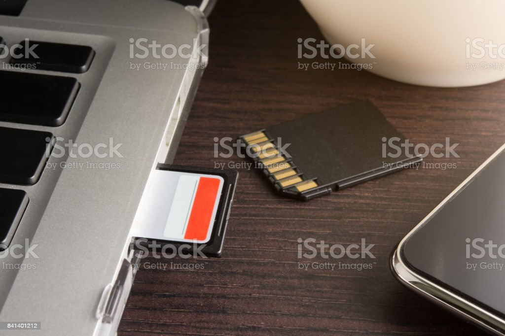 sd card inserted in laptop computer stock photo