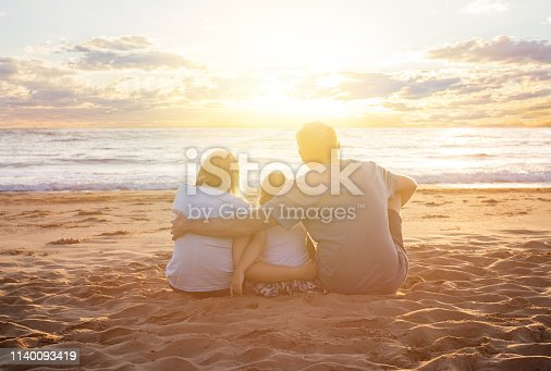 Happy family holidays. Father, mother, baby girl sitting on beach and looking at sunset and sea. People outdoor, summer vacations with children