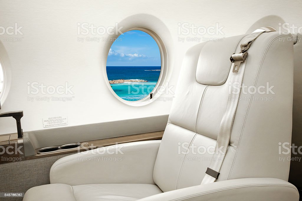 Sea and beach view in aircraft window, business jet flight stock photo