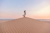 Rear view of young woman with white dress standing and walking on desert sand hill of Patara Beach watching beautiful colorful sunset in Kaş, Kalkan, Antalya, Türkiye