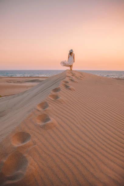 Sea and Desert - Young woman enjoying sunset on the sand hills of Patara, Antalya, Turkey stock photo