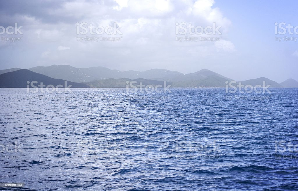 Sea and Hills in The British Virgin Islands View of rolling hills from across the water. Shot in the British Virgin Islands. Blue Stock Photo