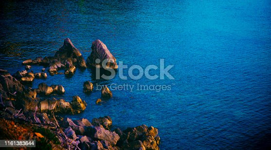 Rocky beach and sea water at sunset
