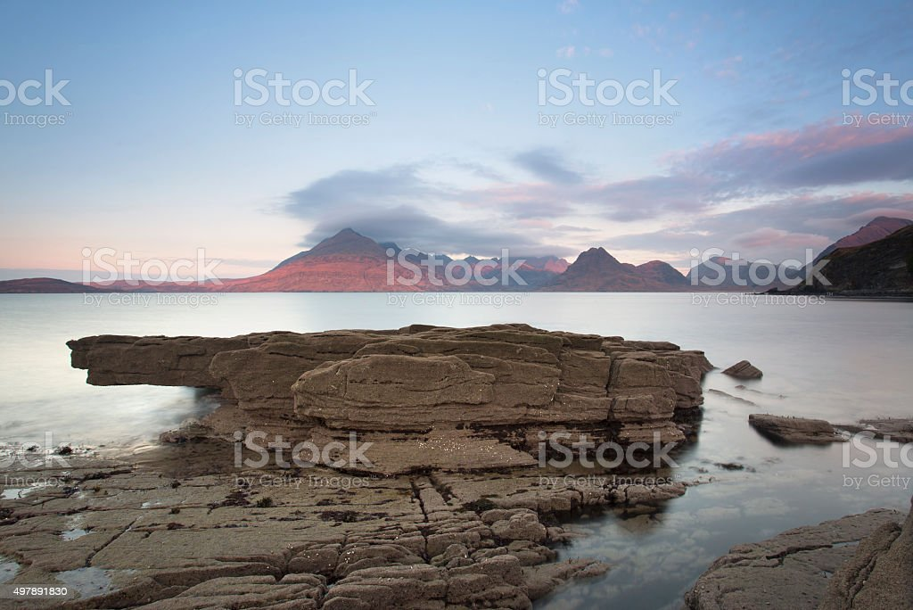 sea and rocky shore with mountains in the background stock photo