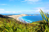 curving sweeping coastline with views from the clifftop, sand dunes, waves and blue sky with clouds
