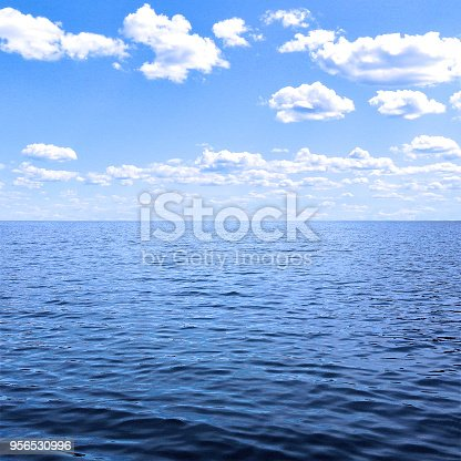 A bright idyllic square full frame background image of relaxing blue ocean waves to the horizon vanishing point with a beautiful blue sky with white clouds.