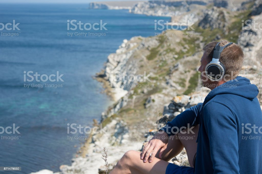 Sea and vacation. Adult man listening to music on headphones. stock photo