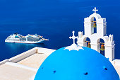 Oia, Santorini, Greece - April 25, 2019: Iconic view of blue and white church dome and bell tower, sea and cruise ship