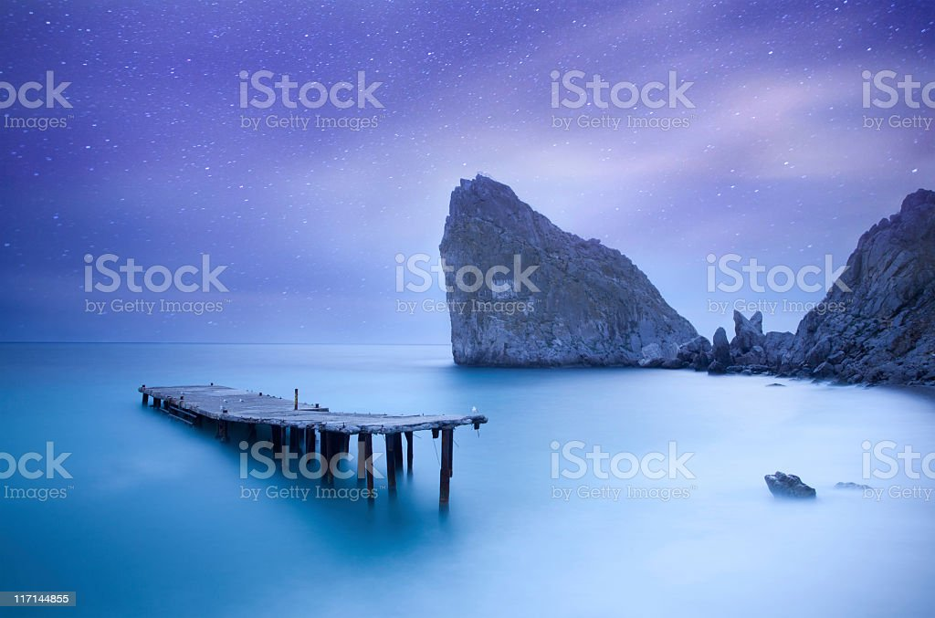 Sea at night under milky way stars with pier royalty-free stock photo