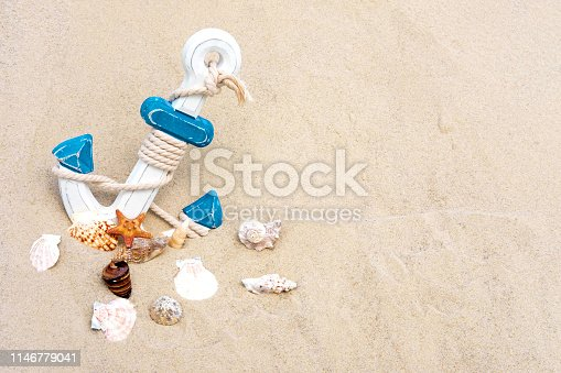 istock Sea background with anchor and seashells. Anchor in the sand. Frame for text tourist, travel banner made of sand with an anchor 1146779041