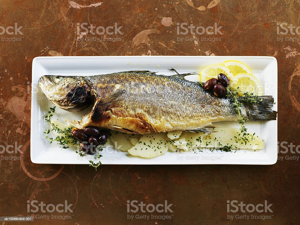 Sea bass roasted with black olives and thyme in plate, close-up, overhead view royalty-free stock photo