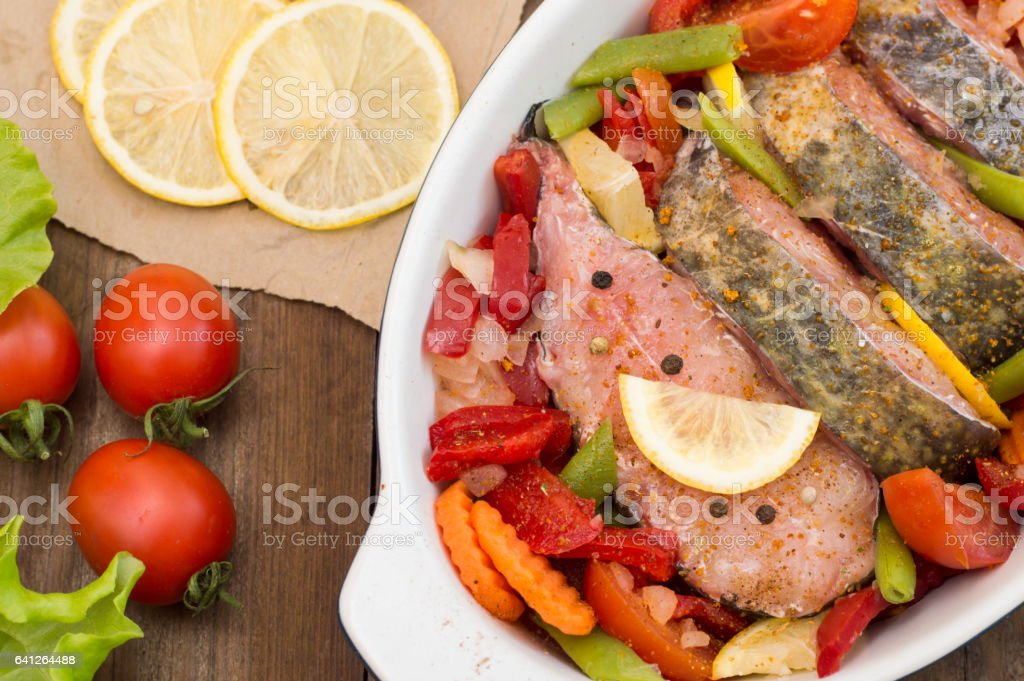 Sea bass with vegetables. marinated fish with vegetables for cooking in the oven. Wooden background. Top view. Close-up stock photo