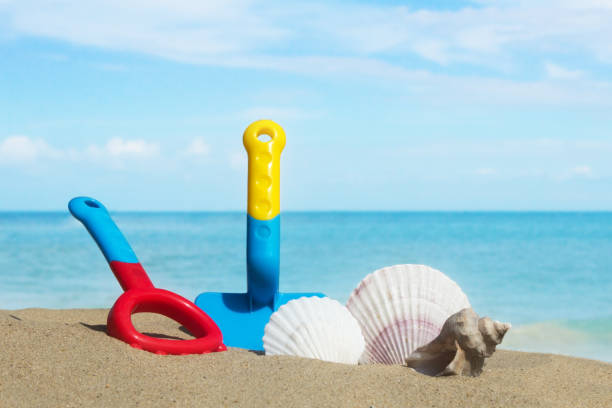 sea beach, clouds,sky,sand,seashells, conch shell and sand toys (summer background) stock photo