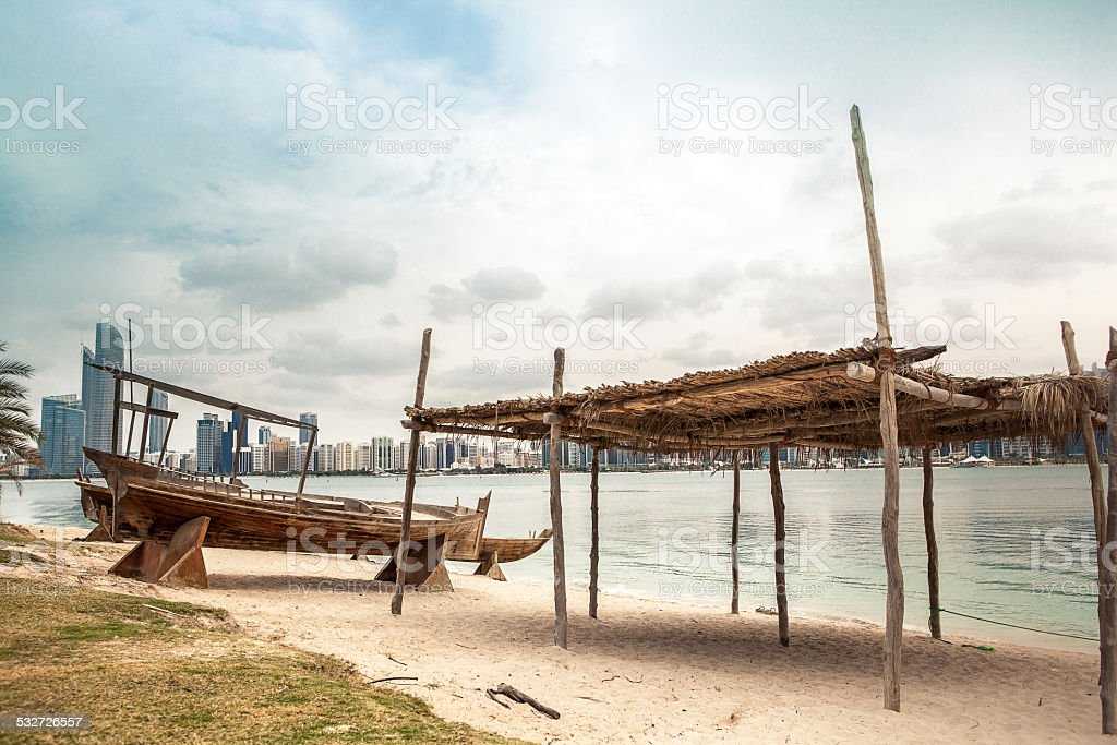 sea beach with old wooden boath and luxury skyscarper stock photo