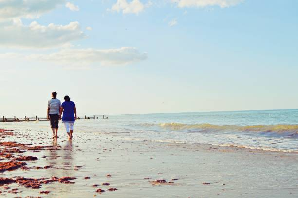A sea beach with waves and an elderly couple taking a walk at some distance stock photo