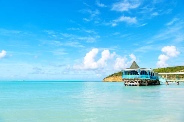 Sea beach with wooden shelter on sunny day in antigua. Pier in turquoise water on blue sky background. Summer vacation on caribbean. Wanderlust, travel, trip. Adventure, discovery, journey stock photo