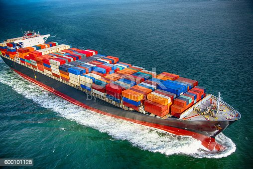 A fully stocked cargo ship heading out to sea.