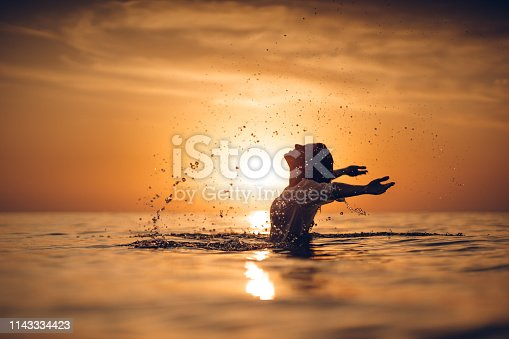 Beautiful woman emerged into the sea is splashing water at sunset