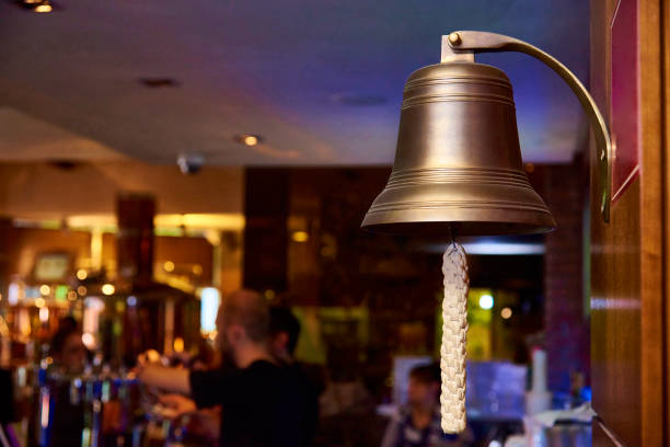 a sea bell with a woven rope on a blurred bar background. - campana foto e immagini stock