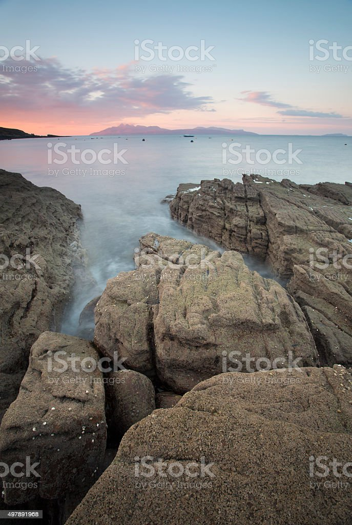 sea breaking against the shore of elgol at sunrise stock photo