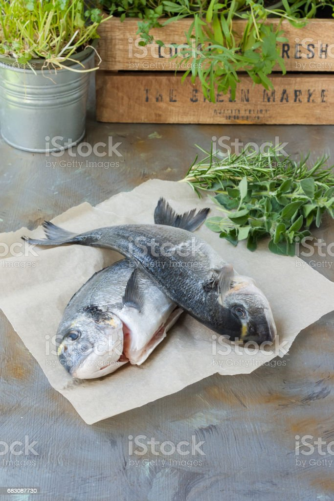 Sea bream fish in cooking process, rustic style foto de stock royalty-free
