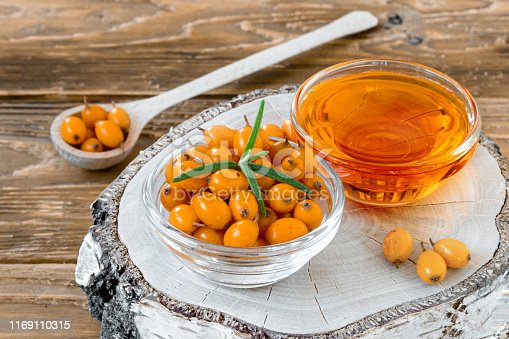 istock Sea buckthorn berries and oil in small glass plates on a birch stump 1169110315